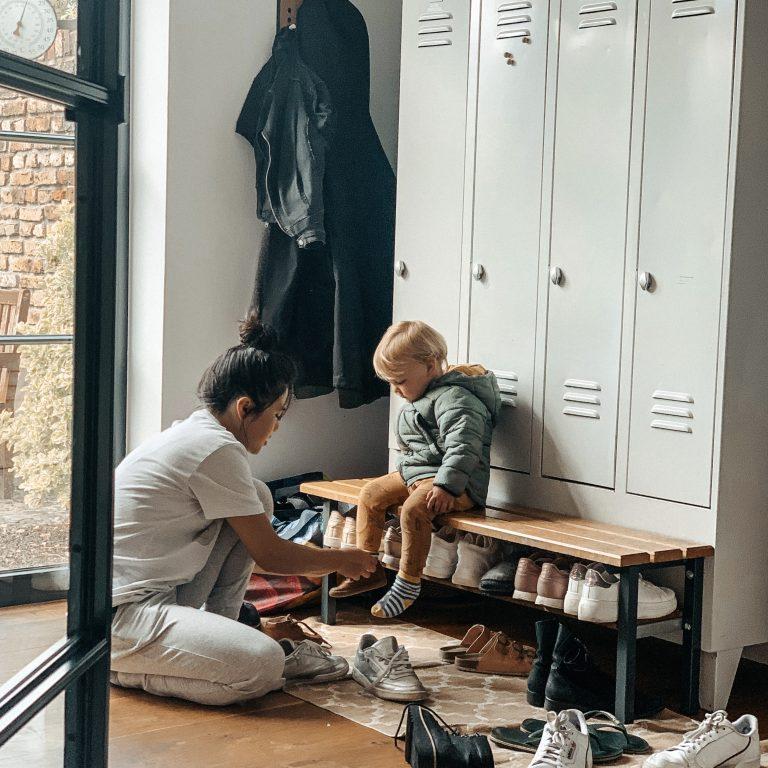 Au pair hilft Kind beim Anziehen der Schuhe