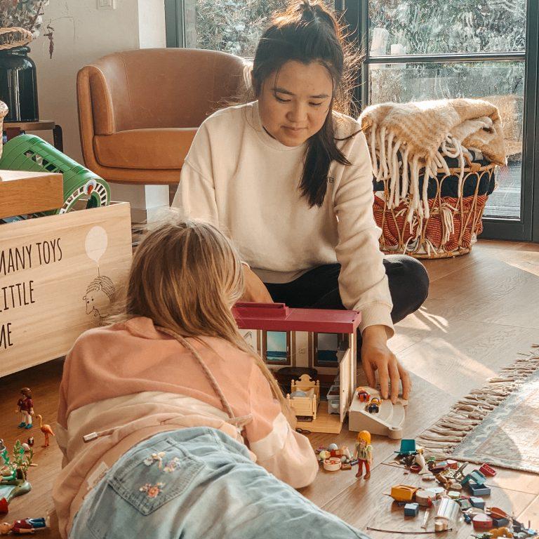Au Pair spielt Playmobil mit einem Kind